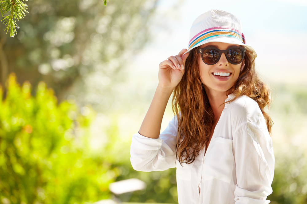 Woman wearing sunglasses and a hat on a sunny summer afternoon