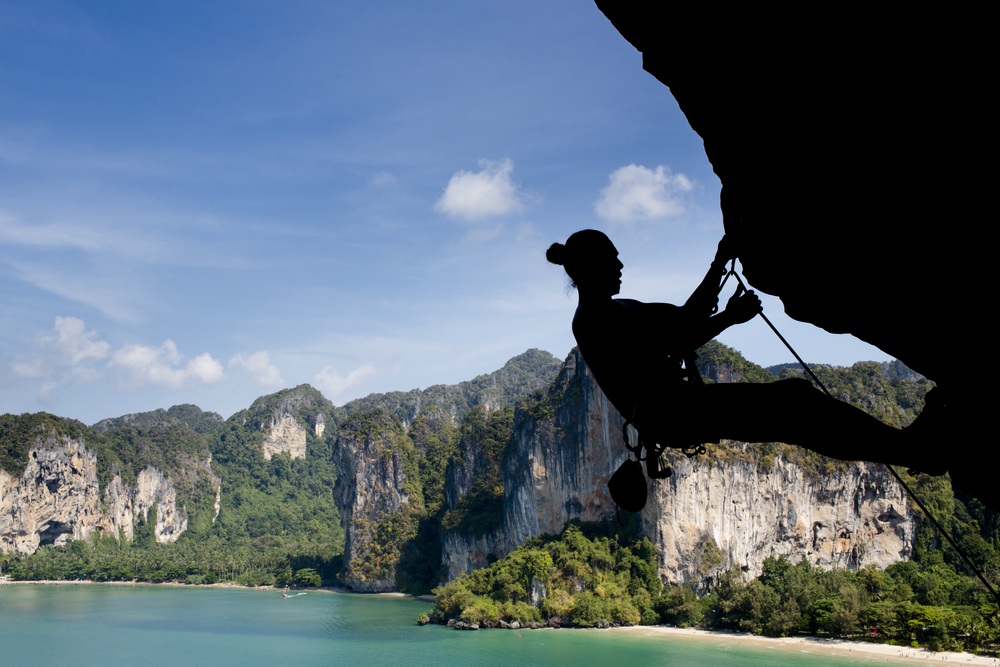 Mountain climber silhouetted against view of Railey Beach in Krabi