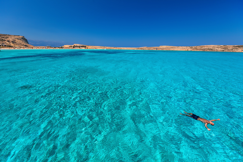 Swimmer floating in crystal clear waters of the Greek Islands
