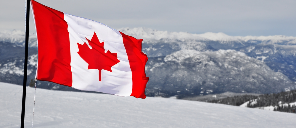 Canada flag with terrain in the background