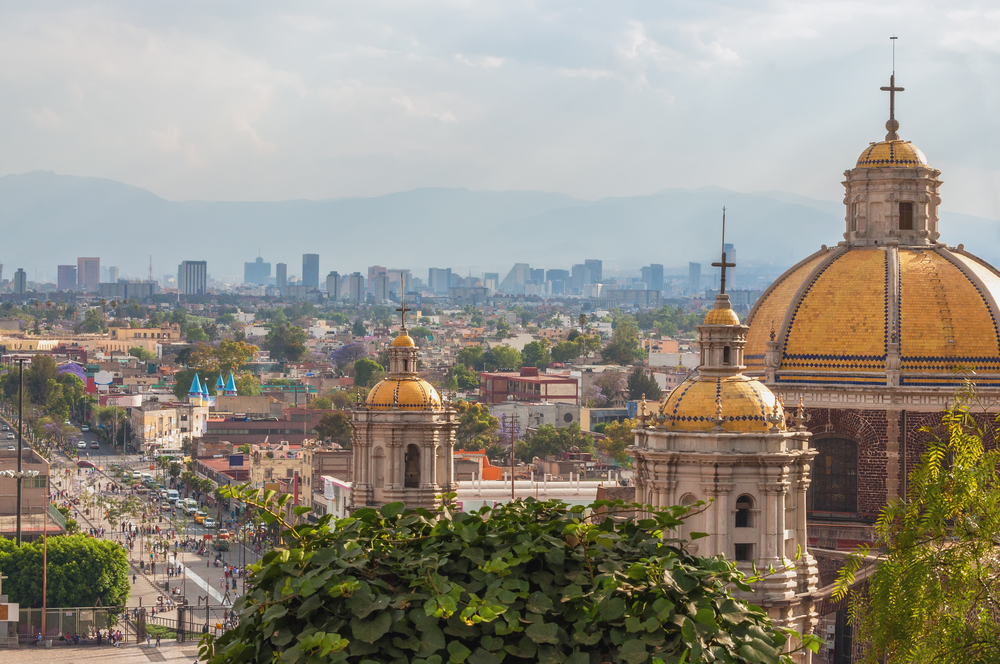 Old Basilica of Guadalupe with Mexico City skyline in the background