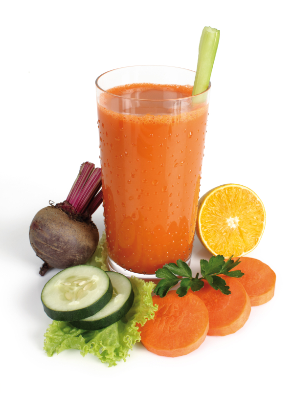 Juicing - cup of fresh squeezed juice surrounded by ingredients