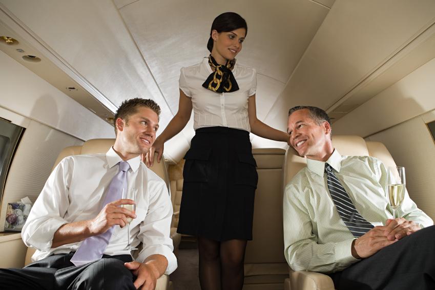 Businessmen and stewardess on jet