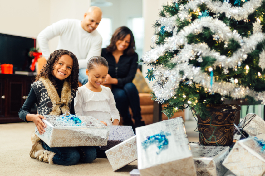 American family celebrates Christmas by opening gifts under the Christmas Tree
