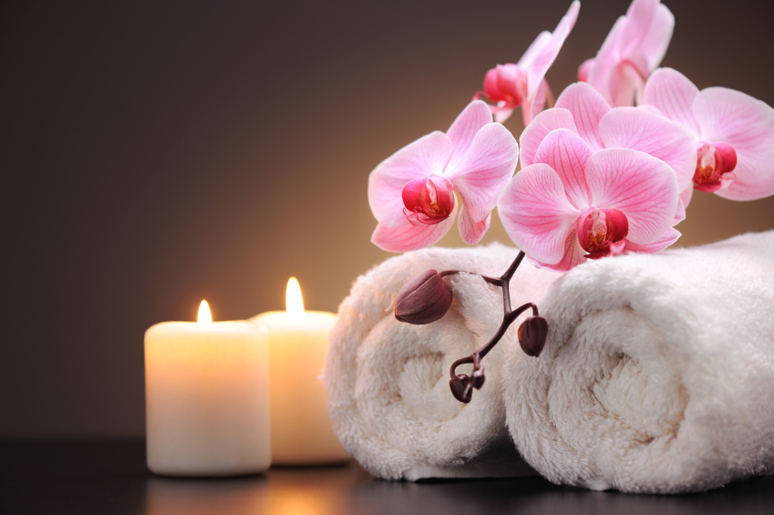Decor at luxury spa with candles, rolled towels and beautiful orchids