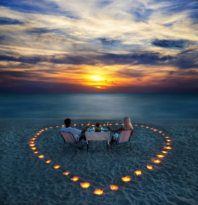 A young couple share a romantic dinner with candles heart on the sea sand beach for their engagement