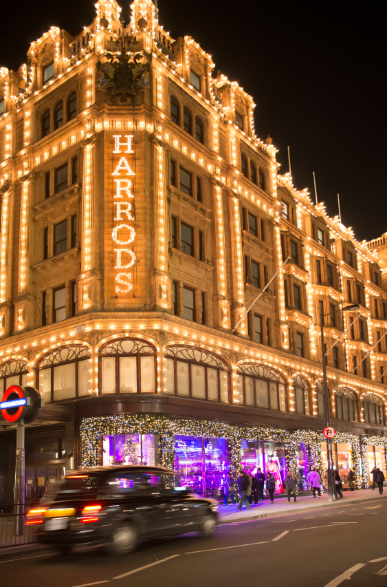 Harrods department store. Facade illuminated at night. Taxi passes in front of the building