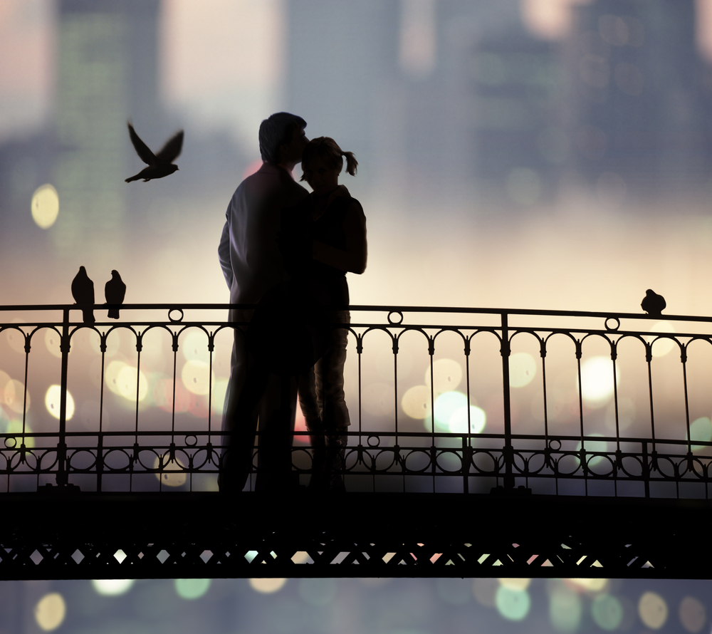 Couple standing on a bridge enjoying a romantic US city