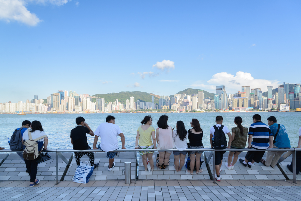People on a bench overlooking the sea in Hong Kong