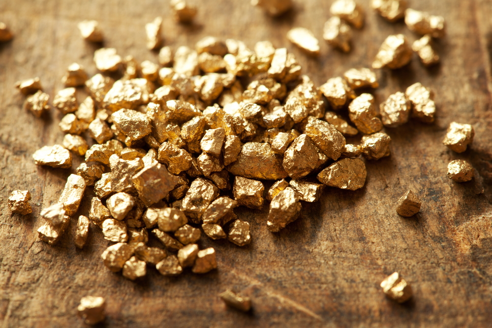 A mound of gold place on a wooden table.