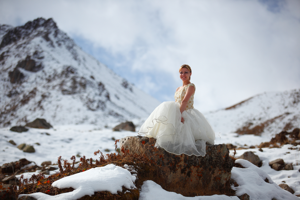 Bride on top of a mountain excited about her wedding.