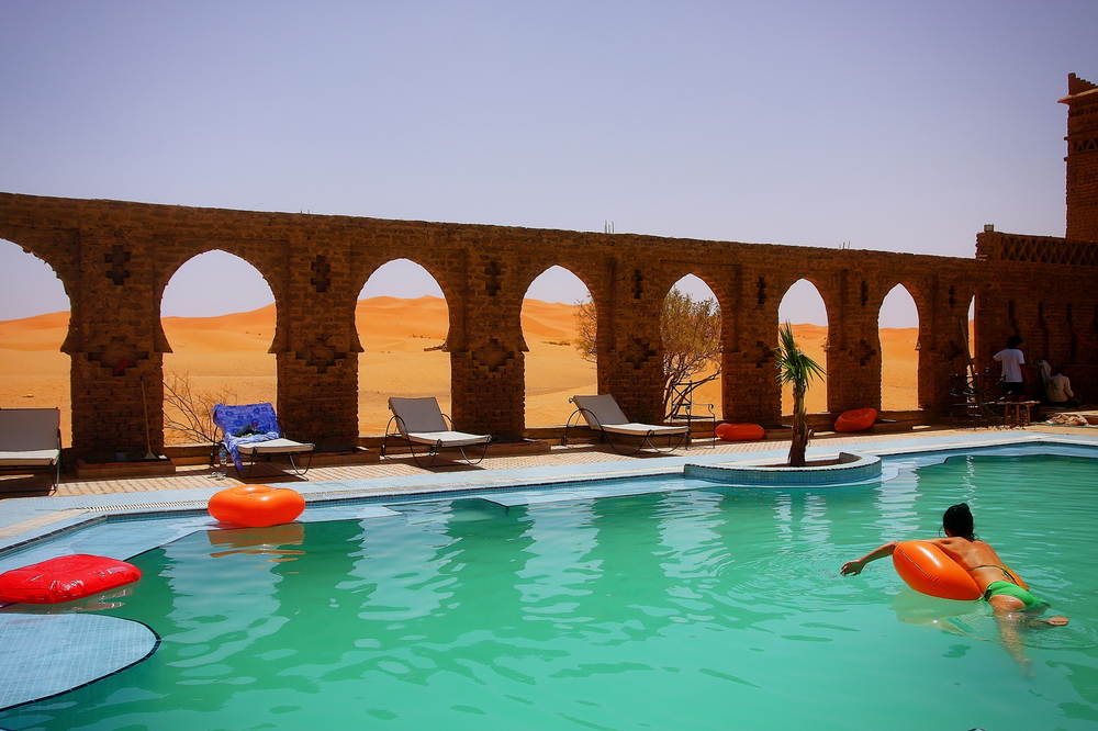 A resort swimming pool that opens out into the desert.