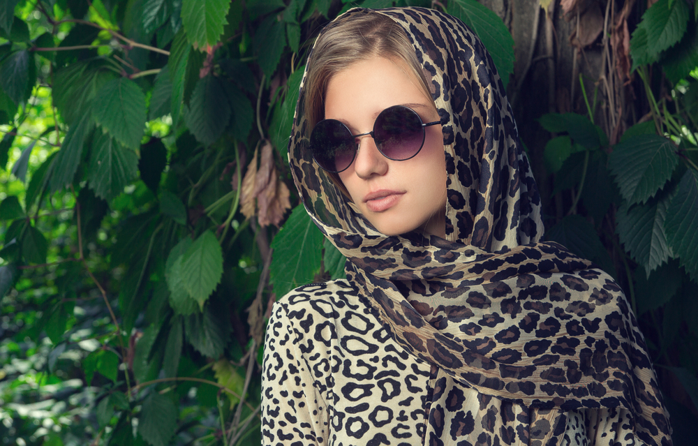 Fashionable woman wearing a sunglass and a scarf.