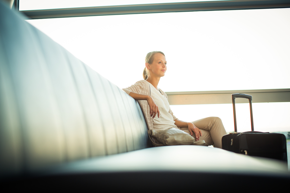 Woman waiting for her flight in an empty waiting lounge.