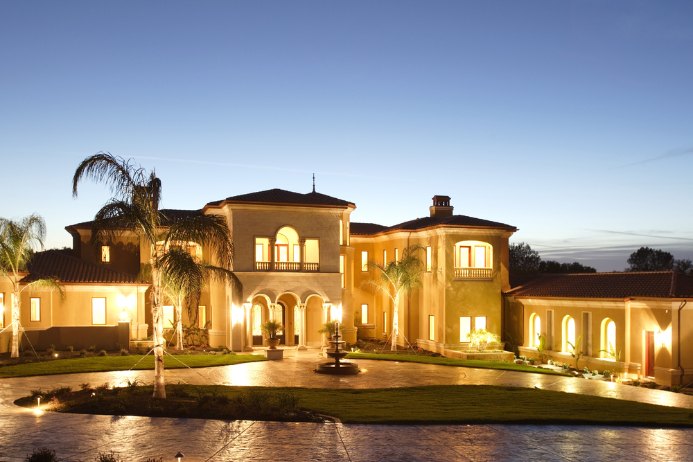 Luxury mansion lit up after sunset.