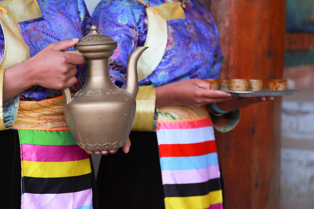Couple serving traditional milk tea in Tibet.