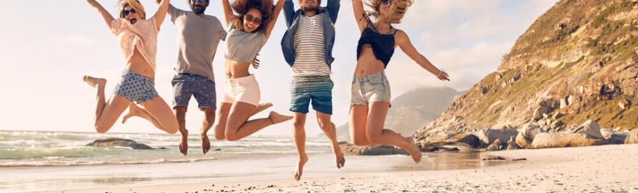 Friends jumping with joy on the beach