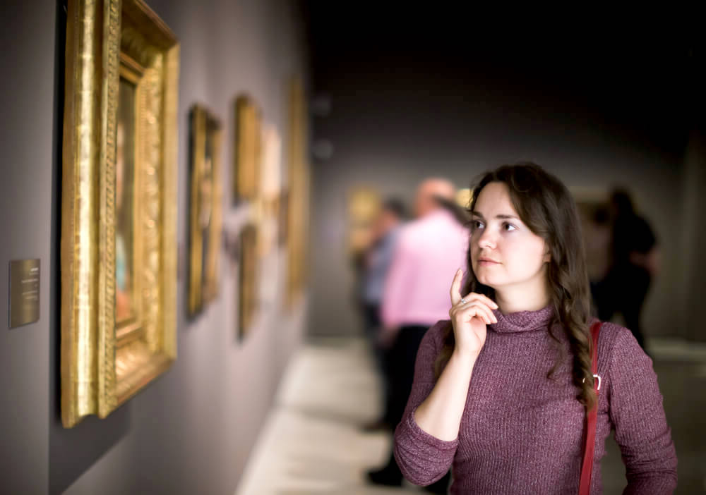 woman admiring artwork in a museum