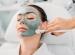 Woman enjoying a clay mask facial treatment at the spa