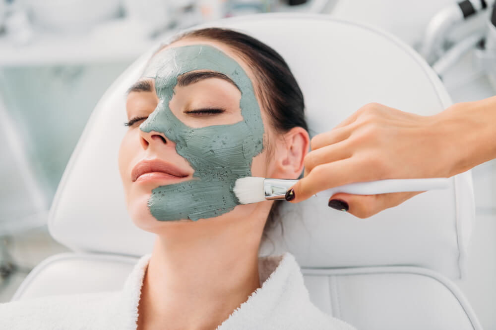Woman enjoying a clay mask facial treatment at the spa
