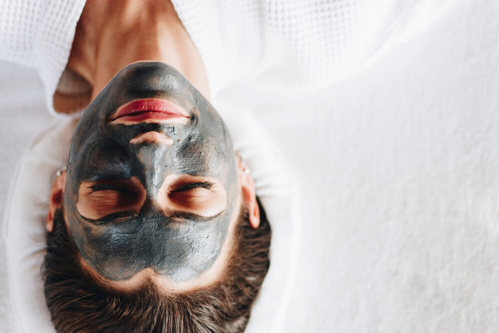 Woman relaxing with a charcoal face mask