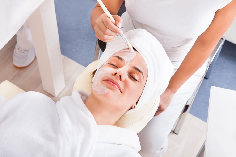 Smiling woman undergoing a facial mask treatment at unknown spa