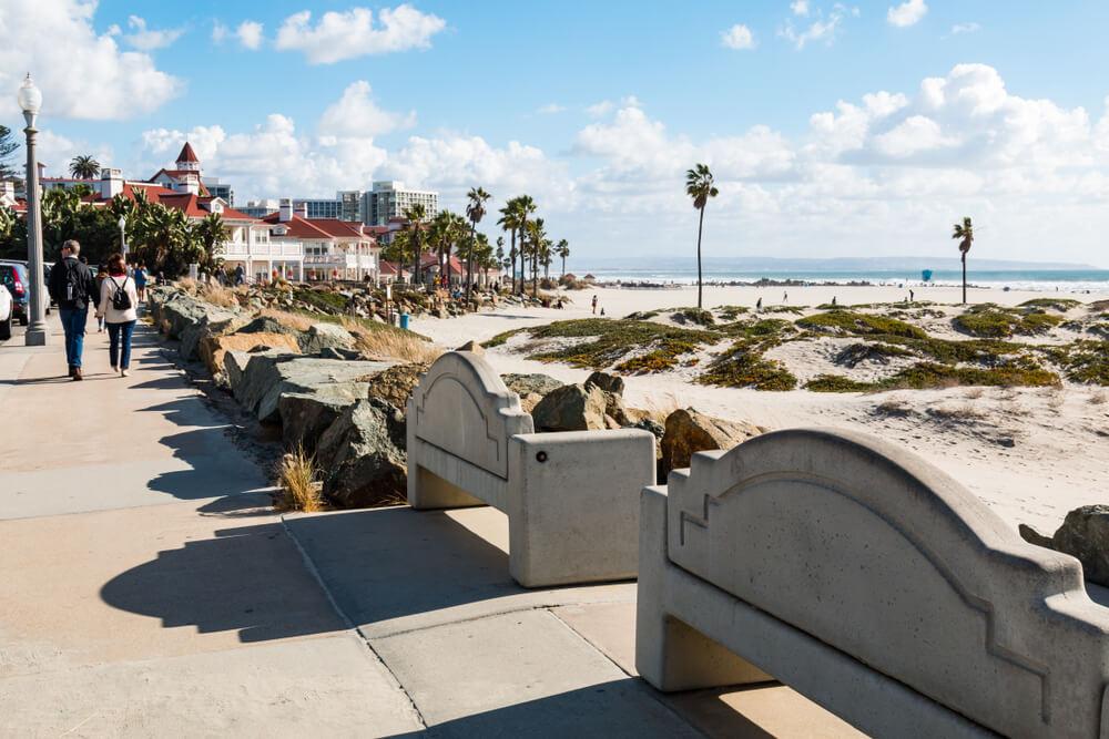CORONADO, CALIFORNIA - JANUARY 20, 2018: People stroll on the boardwalk on Coronado Central Beach, near the historic Hotel Del Coronado, a landmark in the San Diego area, built in 1888